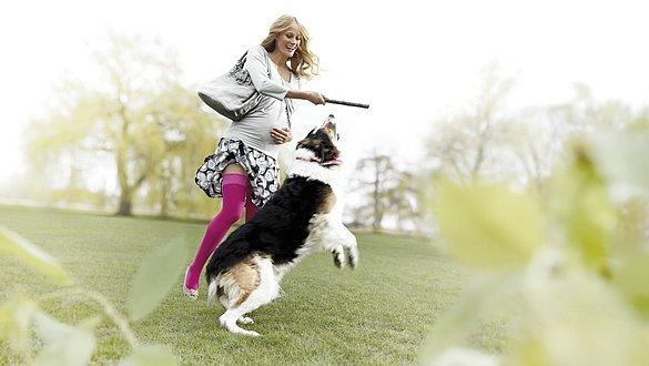 Schwangere trägt mediven elegance beim Spielen mit Hund -